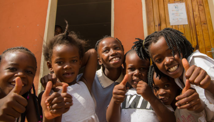 Young girl students shows thumbs up at Tongabezi Trust School
